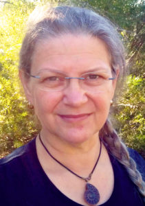 Headshot of a pale-skinned woman outdoors with silvering hair, green leaves in the background. She is wearing spectacles and a neck-choker with a fossilesed ammonite pendant.